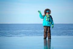 Cute little boy outdoors standing on frozen sea Stock Photos