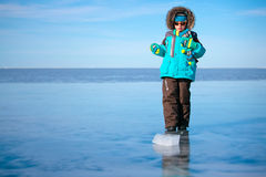 Cute little boy outdoors standing on frozen sea. On beautiful winter day Royalty Free Stock Images
