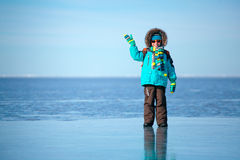 Cute little boy outdoors standing on frozen sea Royalty Free Stock Photography