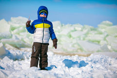 Cute little boy outdoors standing on winter beach. On beautiful winter day Stock Photography