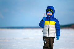 Cute little boy outdoors standing on winter beach. On beautiful winter day Royalty Free Stock Images