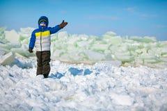 Cute little boy outdoors standing on winter beach Stock Photo