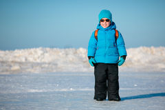 Cute little boy outdoors on winter beach. Portrait of cute little boy outdoors standing on winter beach on cold winter day Stock Photos