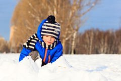 Cute little boy outdoors on winter snow. Day Stock Photo
