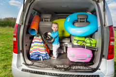 Cute little boy packing luggage standing in boot Stock Photos