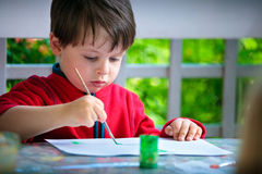 Cute little boy painting with brush Stock Photo