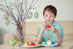 Cute little boy painting colorful Easter egg for hunt Stock Photography