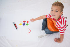 Cute little boy painting on floor in classroom Royalty Free Stock Photography