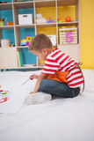 Cute little boy painting on floor in classroom Royalty Free Stock Images