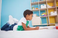 Cute little boy painting on floor in classroom Stock Images