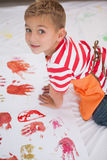 Cute little boy painting on floor in classroom Stock Photography