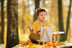 Cute little boy painting in golden autumn park Royalty Free Stock Photo