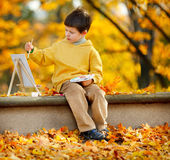 Cute little boy painting in golden autumn park Royalty Free Stock Photography