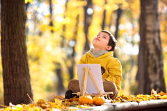 Cute little boy painting in golden autumn park Stock Image