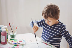 Cute little boy painting in his album Stock Image
