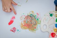 Cute little boy painting with a paint hands using gauche paints stock photography