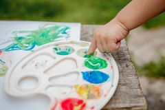 Cute little boy painting with a paint hands using gauche paints stock images