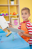 Cute little boy painting at table in classroom Stock Photos