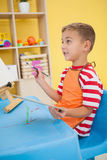 Cute little boy painting at table in classroom Royalty Free Stock Images