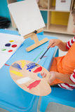 Cute little boy painting at table in classroom Stock Images