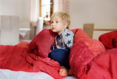 Cute little boy in pajamas having fun in bed after sleeping and watching TV or dreaming. Cozy family weekend at home Stock Photo