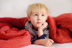 Cute little boy in pajamas having fun in bed after sleeping and watching TV or dreaming. Cozy family weekend at home Royalty Free Stock Photography