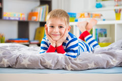 Cute little boy in pajamas lies on bed Royalty Free Stock Image