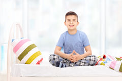Cute little boy in pajamas sitting on a bed Royalty Free Stock Image