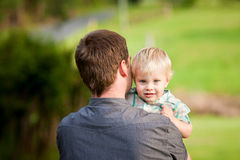 A cute little boy peers over his Dad's shoulder. A cute little blond haired, blue eyed boy plays with his Dad in an outdoor field stock images