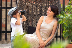 Cute little boy photographing his mother Stock Images