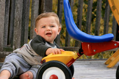 Cute little boy playing. With his tricycle Stock Photos