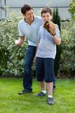 Cute little boy playing baseball with his father Stock Images