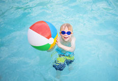 Cute little boy playing with Beach ball in a swimming pool. Having fun and smiling while on vacation. Lots of copy space Royalty Free Stock Images