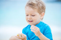 Cute little boy playing on the beach: filling mold shape with sand Royalty Free Stock Photos