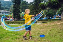 Cute little boy is playing with big bubbles outdoor stock photo