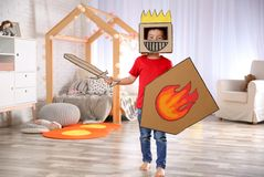 Cute little boy playing with cardboard armor. In bedroom stock photos