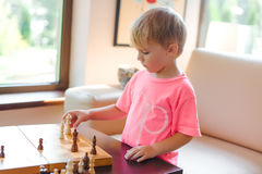 Cute little boy playing chess. Royalty Free Stock Images