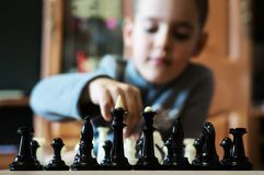 Cute little boy playing chess. The child makes a move chess. home pastime Stock Images