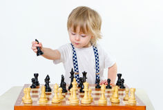 Cute little boy playing chess Stock Photos