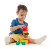 Cute little boy is playing with colorful cups Royalty Free Stock Images
