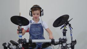 Cute little boy playing drums. Cute little boy wearing headphones playing drums. Adorable child enjoys his music and playing. Museum of popular science and stock footage