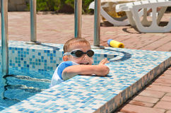 Cute little boy playing at the edge of a pool Royalty Free Stock Photo
