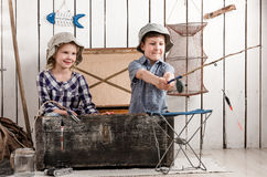 Cute little boy playing fishing with little girl. Cute little boy plays fishing with little girl in big old chest Stock Photos