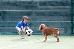 Cute little boy, playing football with his dog. On the playground Royalty Free Stock Image