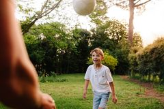 Cute little boy playing football with his father. Father and son in backyard playing with a ball Royalty Free Stock Images