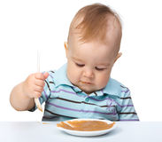 Cute little boy is playing with fruit puree Stock Photo