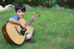 Cute Little Boy Playing Guitar Stock Images