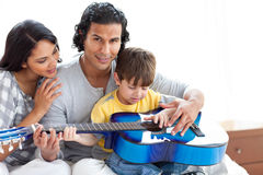 Cute little boy playing guitar with his parents. At home royalty free stock photos