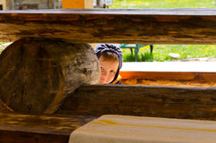 Cute little boy playing hide and seek. Peering out from between wooden beams in a park Stock Photos