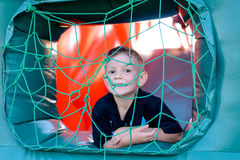 Cute little boy playing in a jumping castle. Peering through the net covering the window in the side grinning at the camera Stock Photography